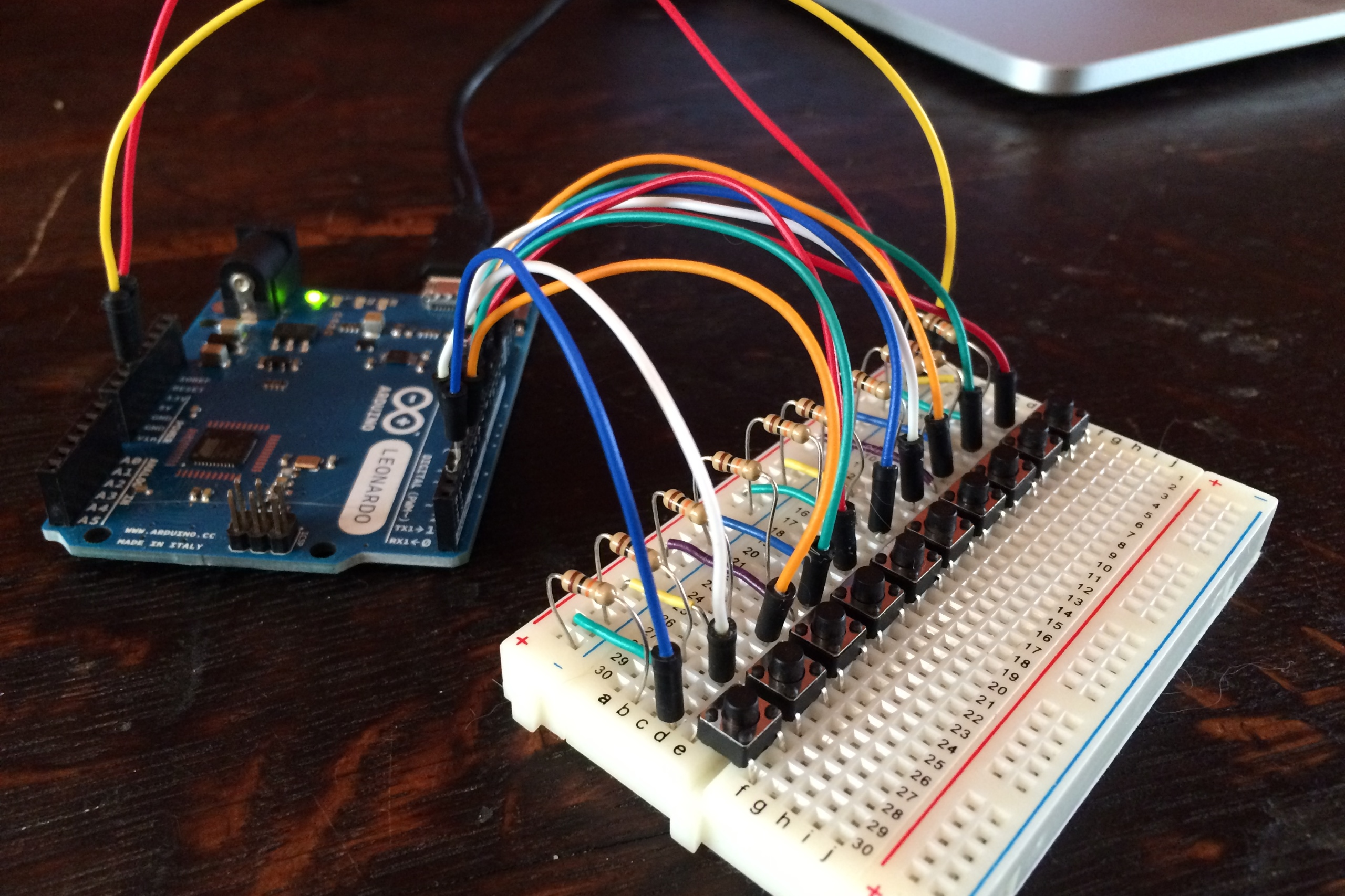 An Arduino Leonardo connected to a breadboard. On the breadboard are 10 buttons, each has a resistor and a wire connected to the arduino. A laptop is in the background.. Picture taken by Steven LeMieux